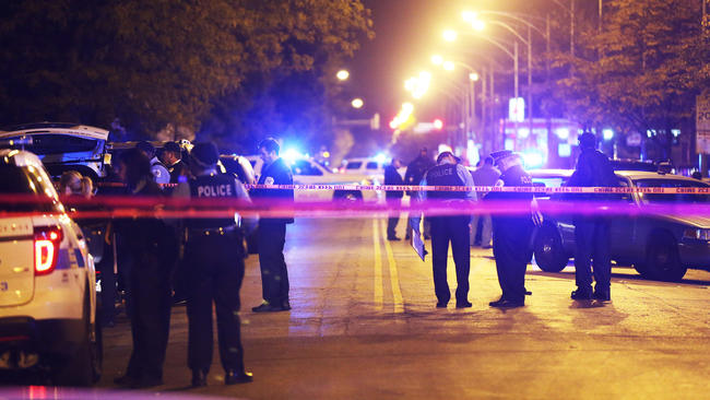 Police investigate at the scene of the fatal police-involved shooting of Ronald Johnson, 25, who was shot Oct. 12, 2014, in the 5300 block of South King Drive in Chicago. (John J. Kim / Chicago Tribune)